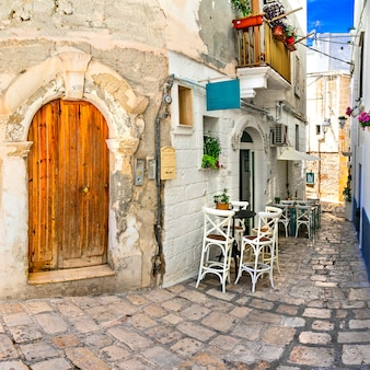 Ruas estreitas tradicionais com bares na cidade branca de puglia. sul da italia