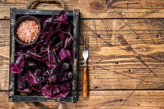 Rubi suíço fresco ou salada de acelga. folhas em uma bandeja de madeira