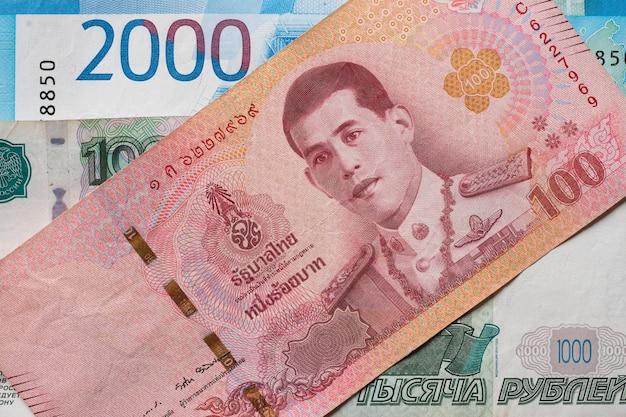 Rublos de russo e close-up do baht tailandês.