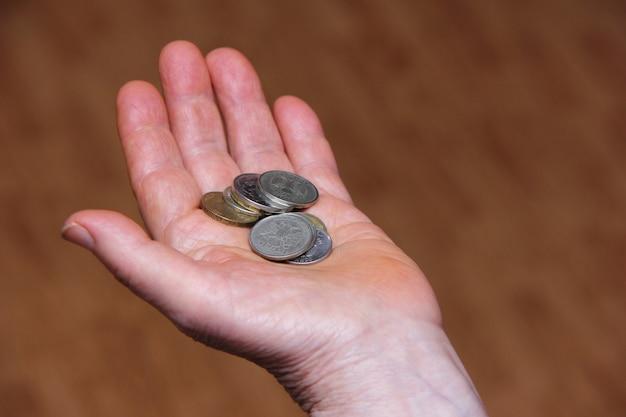 Rublos russos em moedas na mão de uma pessoa idosa.