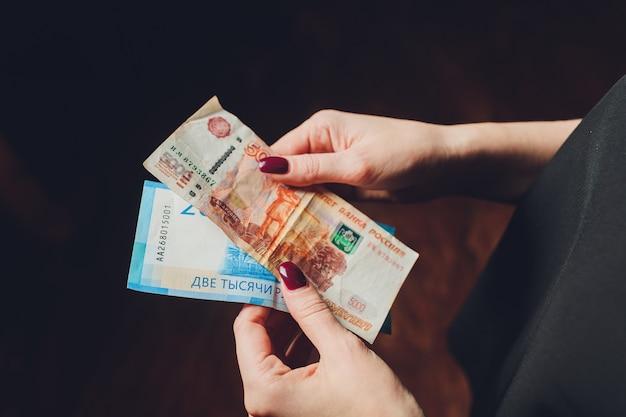 Rublos russos nas mãos de uma mulher de negócios