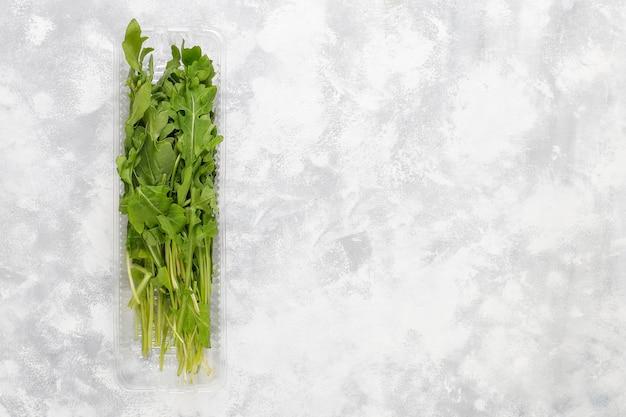 Ruccola verde fresca ou folhas de rúcula em caixas de plástico em concreto cinza