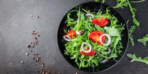 Rúcula e tomate salada de vegetais em um prato porção fresca pronta para comer refeição lanche na mesa