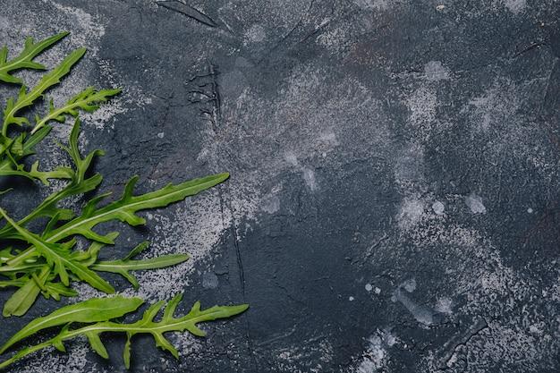 Rúcula no fundo escuro de concreto, conceito de cozinha