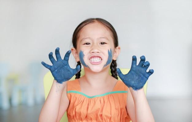 Rugir menina asiática com as mãos azuis na pintura no quarto de crianças