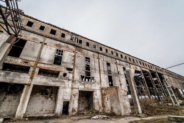 Ruína da velha fábrica e janelas quebradas. edifício industrial para demolição.