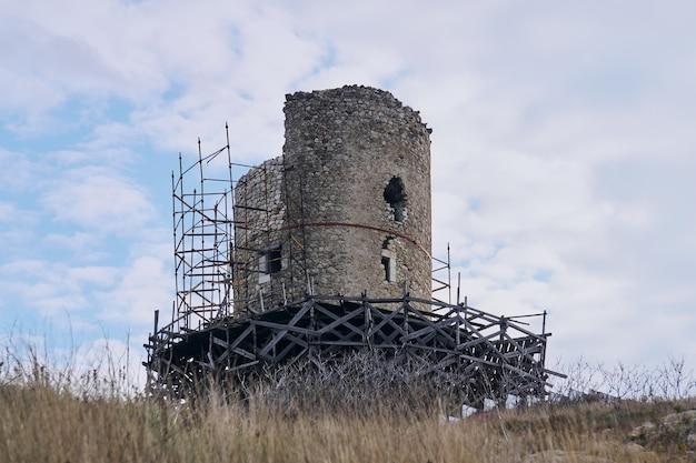 Ruínas da torre da fortaleza medieval no andaime durante a reconstrução