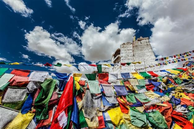 Ruínas do forte da vitória de tsemo no penhasco da colina de namgyal e lungta - bandeiras coloridas de oração budista