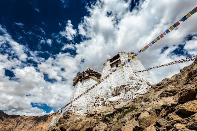 Ruínas do forte da vitória tsemo no penhasco da colina namgyal e bandeiras coloridas de oração budista de lungta