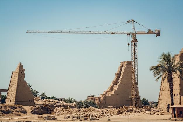 Ruínas e construção no templo de karnak em luxor, egito. guindaste de construção.