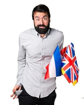 Ruined homem bonito com barba segurando muitas bandeiras e olhando dinheiro em seus bolsos