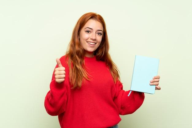 Ruiva adolescente com blusa segurando e lendo um livro