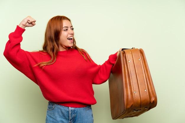 Ruiva adolescente com camisola sobre verde isolado, segurando uma maleta vintage
