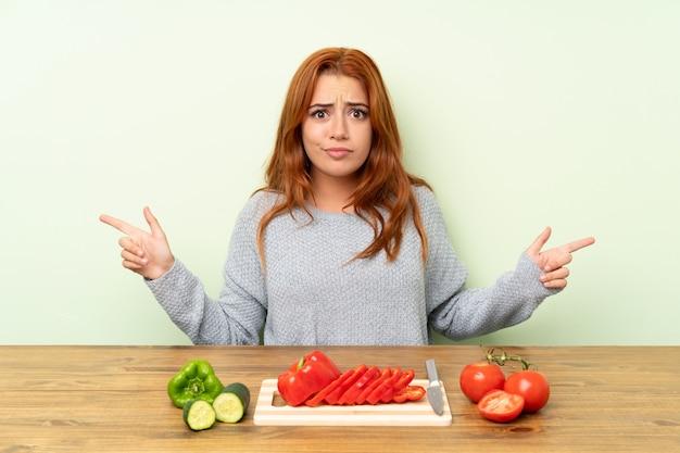 Ruiva adolescente com legumes em uma mesa apontando para as laterais tendo dúvidas
