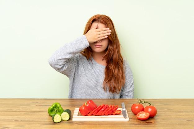 Ruiva adolescente com legumes em uma mesa cobrindo os olhos pelas mãos
