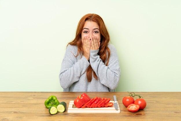 Ruiva adolescente com legumes em uma mesa com expressão facial de surpresa