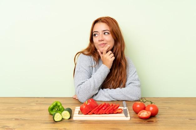 Ruiva adolescente com legumes em uma mesa, pensando uma idéia