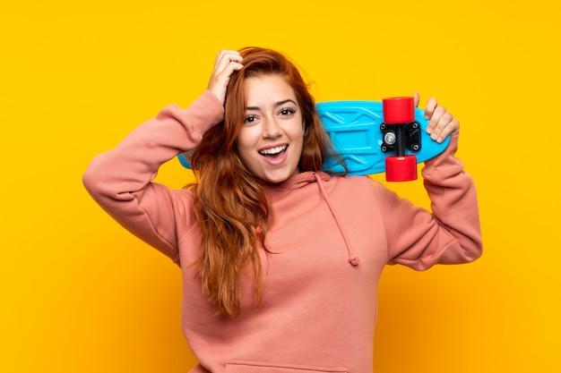 Ruiva adolescente com skate sobre amarelo isolado