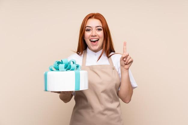 Ruiva adolescente com um bolo grande sobre parede isolada, apontando para cima uma ótima idéia