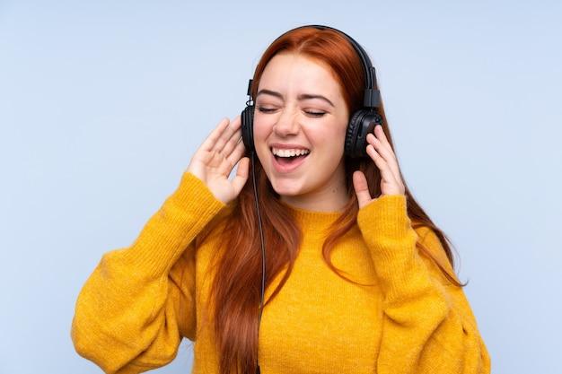 Ruiva adolescente menina com música azul e cantar