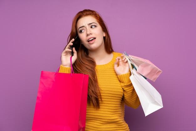 Ruiva adolescente menina isolada parede roxa segurando sacolas de compras e chamando um amigo com seu telefone celular