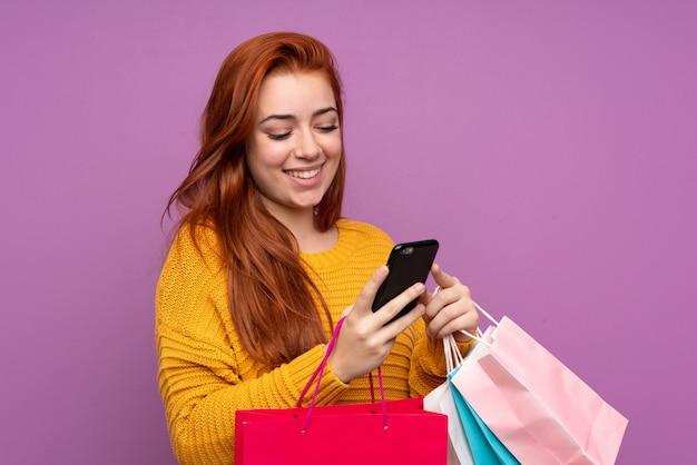 Ruiva adolescente menina isolada parede roxa segurando sacolas de compras e escrever uma mensagem com o celular para um amigo