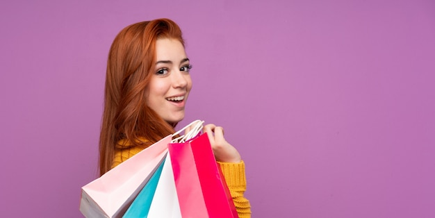 Ruiva adolescente mulher segurando sacolas de compras e sorrindo