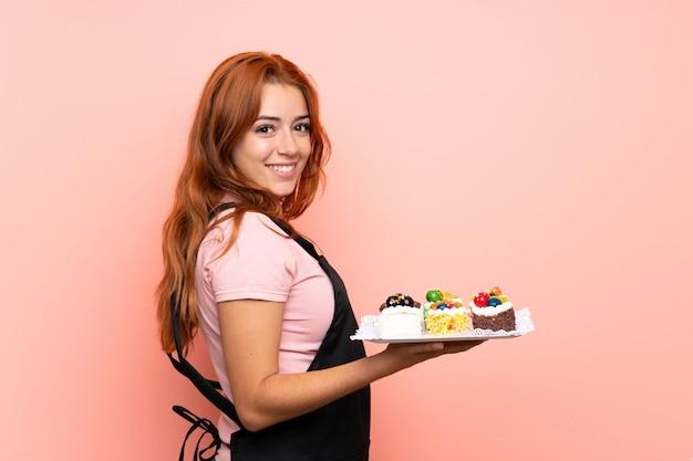 Ruiva adolescente segurando muitos mini bolos diferentes sobre parede rosa isolada, sorrindo muito