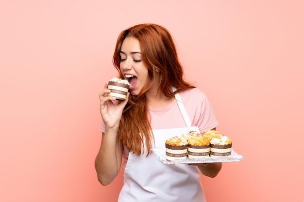 Ruiva adolescente segurando muitos mini bolos diferentes sobre parede rosa isolada