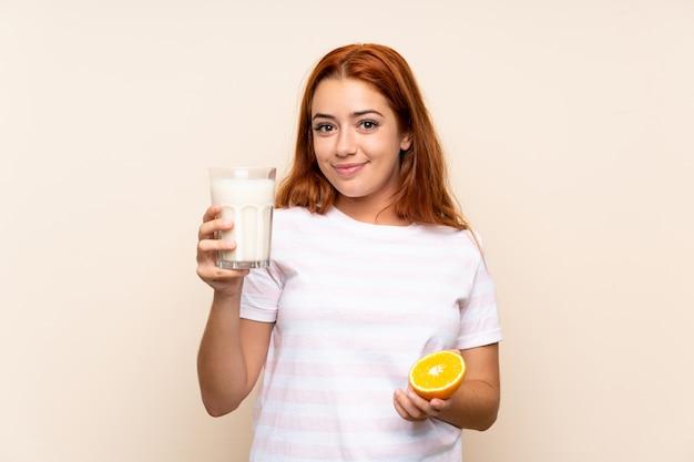 Ruiva adolescente segurando um copo de leite e uma laranja