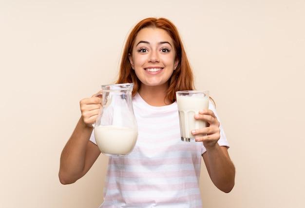 Ruiva adolescente segurando um copo de leite sobre parede isolada
