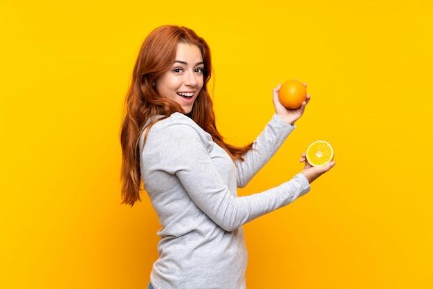 Ruiva adolescente segurando uma laranja sobre parede amarela isolada