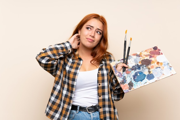 Ruiva adolescente segurando uma paleta sobre parede isolada, pensando uma idéia