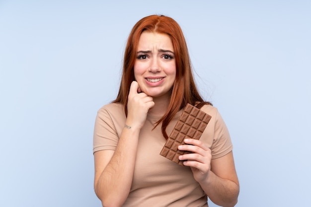 Ruiva adolescente sobre azul tomando uma tablete de chocolate e tendo dúvidas
