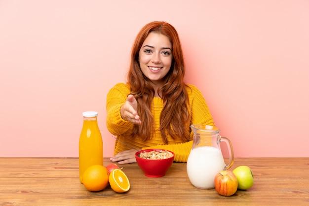 Ruiva adolescente tomando café da manhã em um aperto de mão da mesa depois de um bom negócio