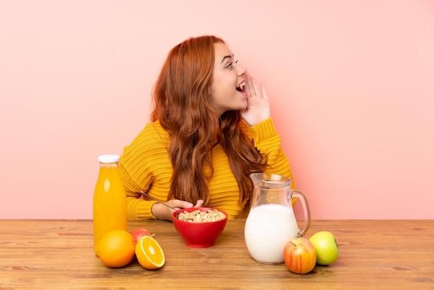 Ruiva adolescente tomando café da manhã em uma mesa gritando com a boca aberta