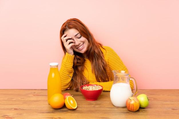 Ruiva adolescente tomando café da manhã em uma mesa rindo