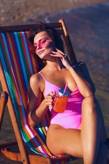 Ruiva atraente em uma chaise longue tomando sol perto do mar com um copo de suco na mão