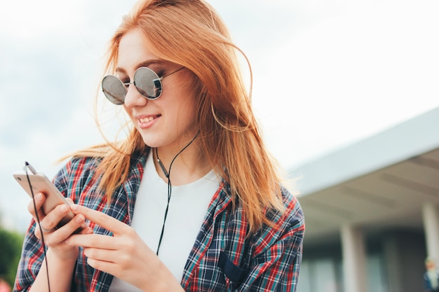 Ruiva atraente garota sorridente em óculos de sol redondos com telefone nas mãos em roupas casuais, ouvindo música