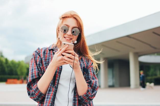 Ruiva atraente garota sorridente em óculos de sol redondos com telefone nas mãos
