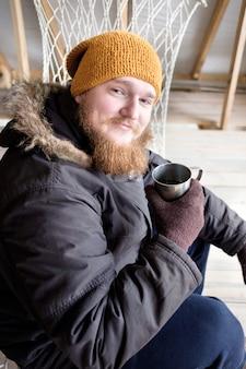 Ruiva barbudo homem de casaco polar, segurando a xícara de café quente ou chá e sorrindo