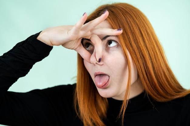 Ruiva bonita engraçada mostrando sinal de mau cheiro com os dedos.