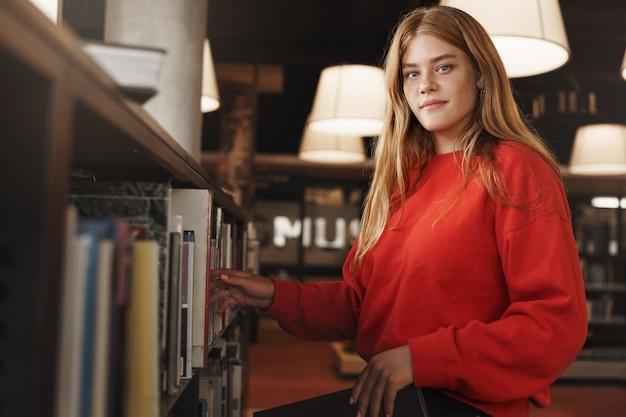 Ruiva bonita, estudante universitária escolhe um livro da prateleira da biblioteca ou livraria, sorrindo para a câmera.