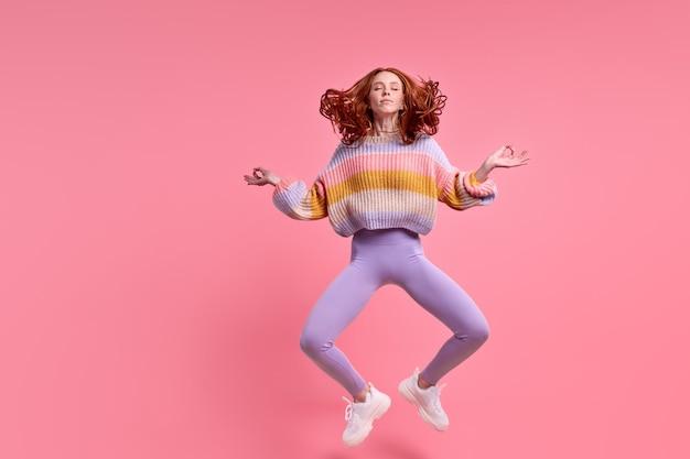 Ruiva bonita pulando sentado no ar em posição de lótus praticando ioga matinal, vestindo roupa casual isolado fundo de cor rosa pastel, retrato. mulher caucasiana calma meditando