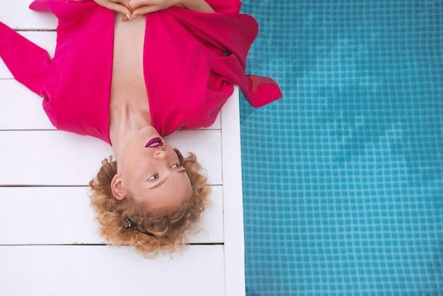 Ruiva cacheada jovem deitada com uma jaqueta fúcsia à beira da piscina