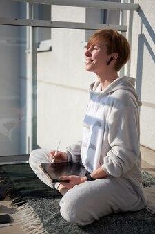 Ruiva caucasiana menina sentada na manta na varanda com tablet e sorrindo para o sol da manhã