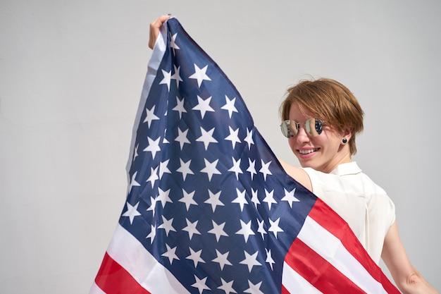 Ruiva caucasiana sorridente detém eua bandeira atrás das costas
