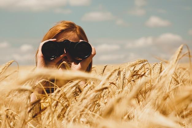 Ruiva com binóculo no campo de trigo