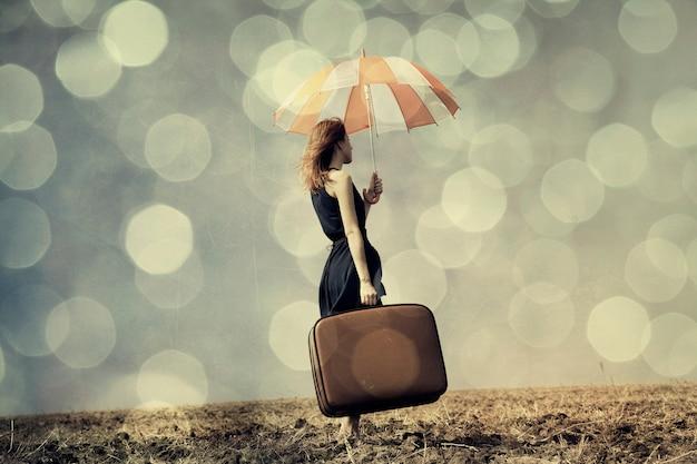 Ruiva com guarda-chuva e mala no campo ventoso