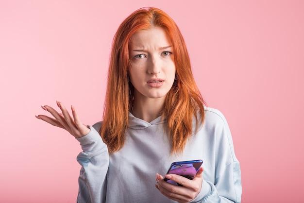 Ruiva confusa com o telefone no estúdio em fundo rosa